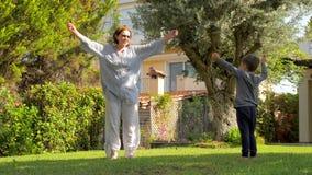 Grand-mère avec le petit-fils faisant des sports sur l'arrière-cour, cour Grand-mère gaie ayant l'amusement avec le petit-fils ex banque de vidéos