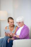 Grand-mère avec sa petite-fille s'asseyant sur un sofa Photo stock