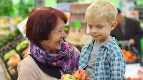 Grand-mère avec son petit petit-fils acheter les pommes fraîches dans un grand supermarché banque de vidéos