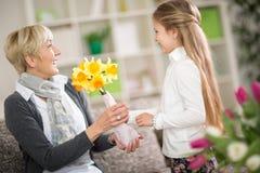 Grand-mère avec un bouquet des fleurs reçues du granddaughte Image stock
