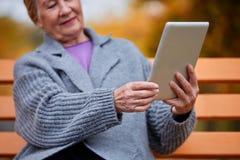 Grand-mère avec un comprimé sur un banc en parc Photographie stock libre de droits