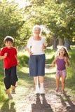 Grand-mère courant en stationnement avec des enfants Photo stock