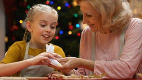 Grand-mère de aide d'enfant pour décorer des biscuits de pain d'épice, pâtisseries faites maison clips vidéos