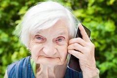 Grand-mère de sourire heureuse parlant au téléphone portable Images stock