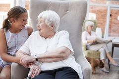Grand-mère de visite de petite-fille dans la maison de retraite photographie stock