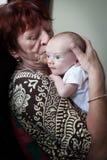 Grand-mère embrassant le petit-fils nouveau-né Photographie stock libre de droits