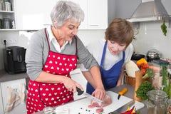 Grand-mère enseignant le jeune garçon à faire cuire la viande - vie de famille au hom Images libres de droits