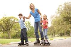 Grand-mère et enfants patinant en stationnement Photo stock