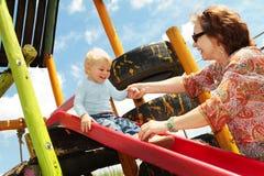 Grand-mère et fils sur la cour de jeu Image libre de droits
