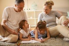 Grand-mère et grands-pères enseignant leur petite-fille au wri image libre de droits