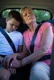 Grand-mère et petit-fils détendant dans le siège arrière de la voiture Images stock