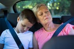 Grand-mère et petit-fils détendant dans le siège arrière de la voiture Photos stock