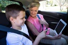 Grand-mère et petit-fils employant le siège arrière numérique du comprimé n de la voiture Image libre de droits