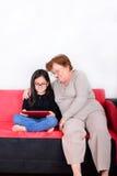 Grand-mère et petite-fille à l'aide de la tablette Images stock