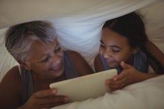 Grand-mère et petite-fille à l'aide du comprimé numérique dans la chambre de lit Images stock