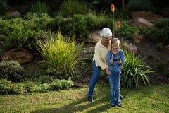 Grand-mère et petite-fille à l'aide du téléphone portable dans le jardin Photo stock
