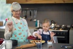 Grand-mère et petite-fille ajoutant des fraises à la croûte Image stock
