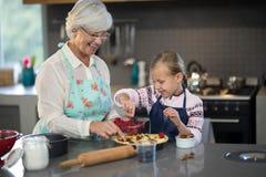 Grand-mère et petite-fille ajoutant des fraises à la croûte Photographie stock libre de droits