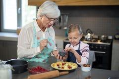 Grand-mère et petite-fille ajoutant les baies bleues à la croûte Photographie stock