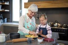 Grand-mère et petite-fille ajoutant les pommes fraîches de coupe à la croûte Photos libres de droits
