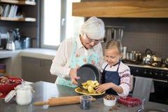 Grand-mère et petite-fille ajoutant les pommes fraîches de coupe à la croûte Image libre de droits