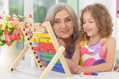 Grand-mère et petite-fille apprenant à utiliser l'abaque Image libre de droits
