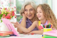 Grand-mère et petite-fille apprenant à utiliser l'abaque Image stock