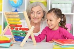 Grand-mère et petite-fille apprenant à utiliser l'abaque Photographie stock libre de droits