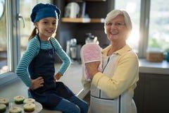 Grand-mère et petite-fille avec des gants de four dans la cuisine Photos stock