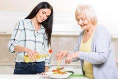 Grand-mère et petite-fille faisant la salade photo stock