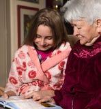 Grand-mère et petite-fille lisant un livre Photos stock