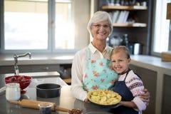 Grand-mère et petite-fille posant avec les pommes fraîches de coupe sur la croûte Photos libres de droits