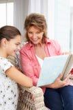 Grand-mère et petite-fille regardant des photos Image libre de droits
