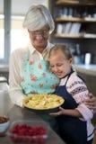 Grand-mère et petite-fille regardant les pommes fraîches de coupe sur la croûte Images libres de droits