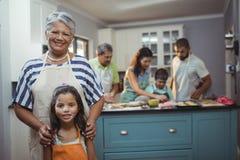 Grand-mère et petite-fille souriant à l'appareil-photo tandis que membres de la famille préparant le dessert à l'arrière-plan photo stock