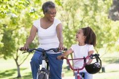 Grand-mère et petite-fille sur des vélos à l'extérieur Images stock