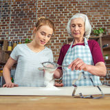 Grand-mère et petite-fille tamisant la farine Images libres de droits