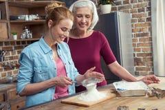Grand-mère et petite-fille tamisant la farine Photo stock