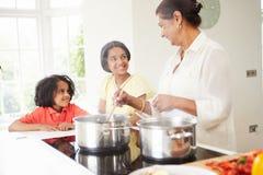 Grand-mère et petits-enfants faisant cuire le repas à la maison Image libre de droits