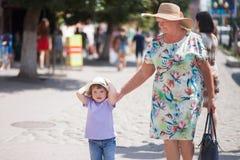 Grand-mère et sa petite-fille marchant dans la ville, prenant du temps ensemble Image libre de droits