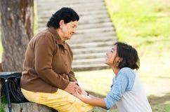 Grand-mère faisant face aux têtes émouvantes de petite-fille Photos stock