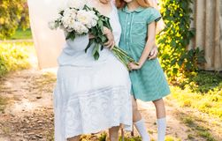 Grand-mère, femme agée reposant et étreignant sa petite-fille, fille et tenir un bouquet des fleurs dans le jardin betwee d'amour Photo libre de droits