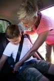 Grand-mère fixant son petit-fils avec la ceinture de sécurité Image stock