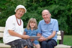 Grand-mère, grand-père et petite-fille à l'aide du comprimé Photographie stock libre de droits