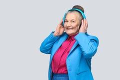 Grand-mère heureuse à la mode dans le style occasionnel coloré tenant son bl photo libre de droits