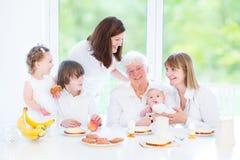 Grand-mère heureuse appréciant le petit déjeuner avec sa famille Image stock