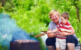Grand-mère heureuse avec de la viande de torréfaction de petit-enfant sur le pique-nique Photo stock