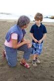 Grand-mère heureuse causant avec le petit-fils sur une plage Photographie stock
