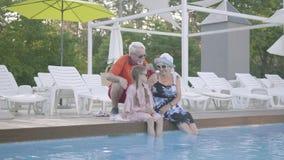 Grand-mère heureuse de joie, grand-père et peu de petite-fille ayant un repos par la piscine de luxe banque de vidéos