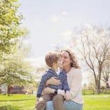 Grand-mère heureuse embrassant le petit-fils en parc Images stock